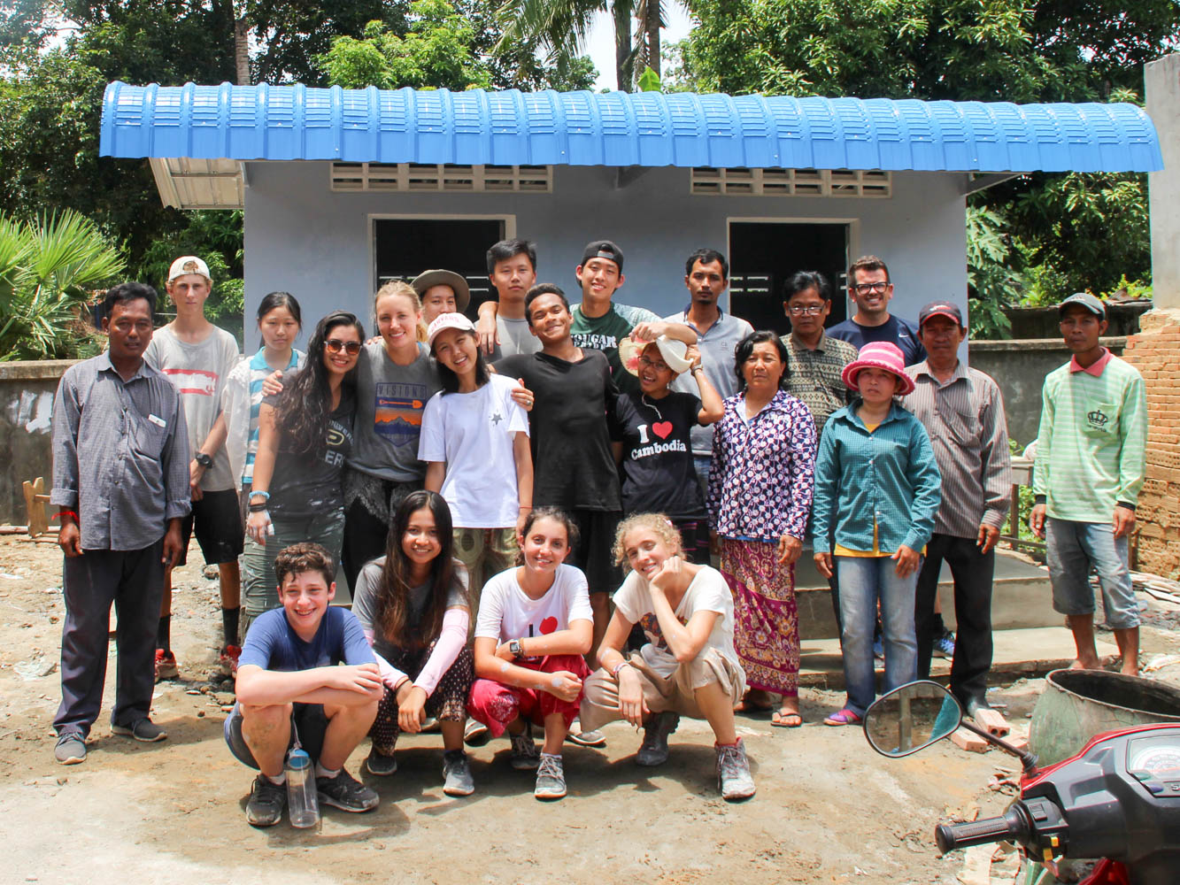 Community service group posing in front of construction project on a Cambodia teen service trips